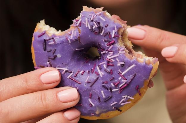 Gros plan, femme, manger, violet, beignet Photo gratuit