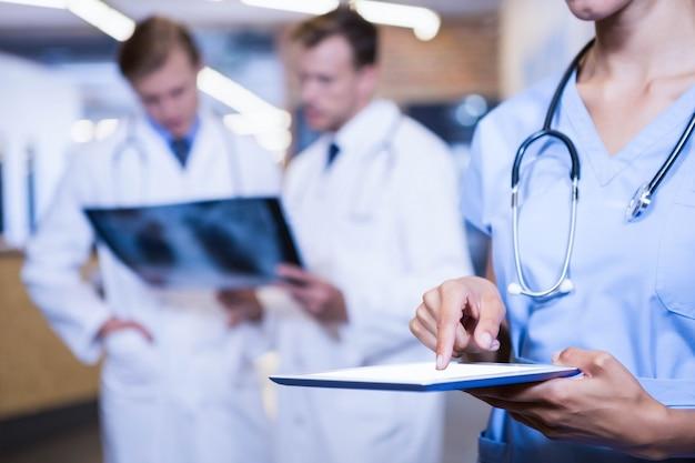 Gros plan d'une femme médecin à l'aide d'une tablette numérique à l'hôpital Photo Premium
