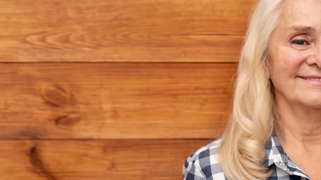 Gros plan femme avec mur en bois comme toile de fond Photo gratuit