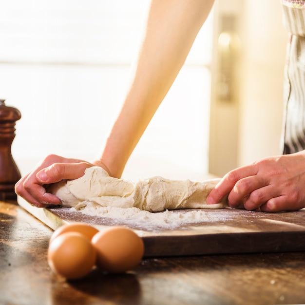 Gros plan, femme, pétrir, pâte, couper, planche bois Photo gratuit