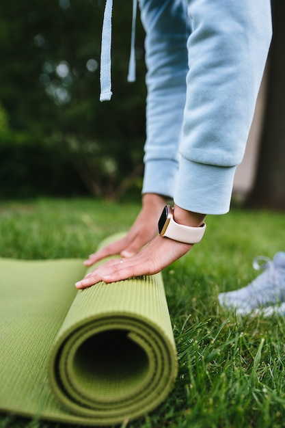 Gros Plan, De, Femme, Pliage, Rouleau, Fitness, Ou, Yoga, Tapis, Après, Séance, Dans Parc Photo gratuit
