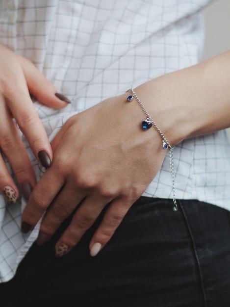 Gros Plan D'une Femme Portant Un Bracelet à Breloques En Argent à La Mode Photo gratuit