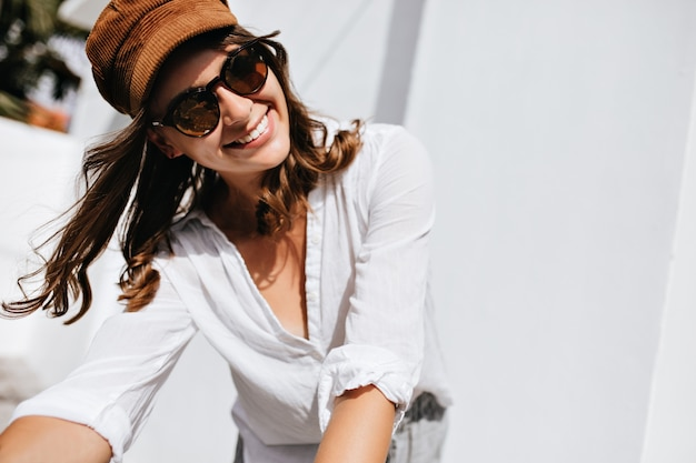 Gros Plan D'une Femme Posant Dans La Rue. Fille En Tenue D'été élégante Et Coiffe Sourit Contre L'espace De La Maison Lumineuse. Photo gratuit