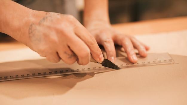 Gros plan, de, femme, potier, main, couper, argile, à, règle, et, outil Photo gratuit