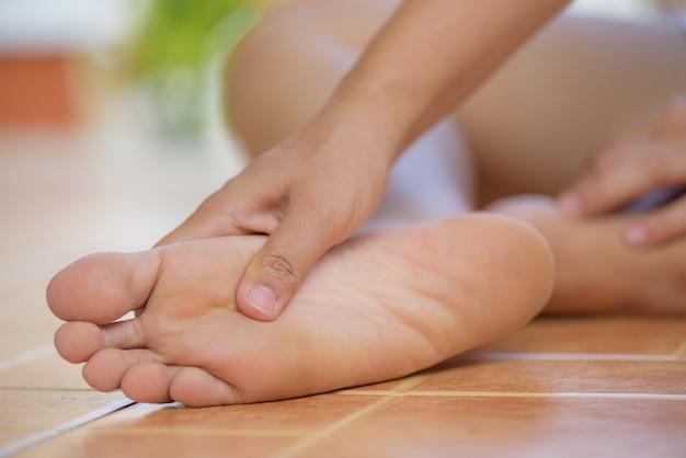 Gros plan femme ressentir de la douleur dans son pied à la maison. concept de soins de santé. Photo Premium