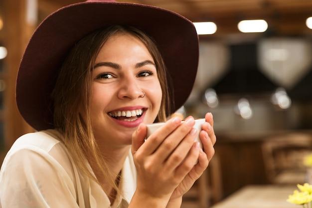 Gros Plan D'une Femme En Riant Au Chapeau Assis Au Café Photo Premium