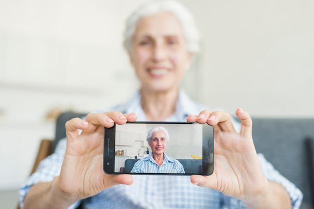 Gros plan d'une femme senior montrant sa photo sur smartphone Photo gratuit