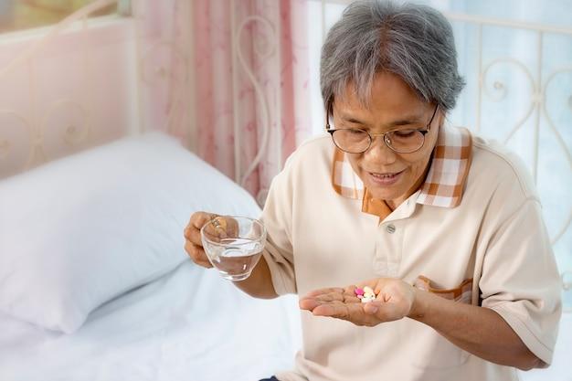 Gros plan d'une femme senior avec des pilules et un verre d'eau à la maison Photo Premium