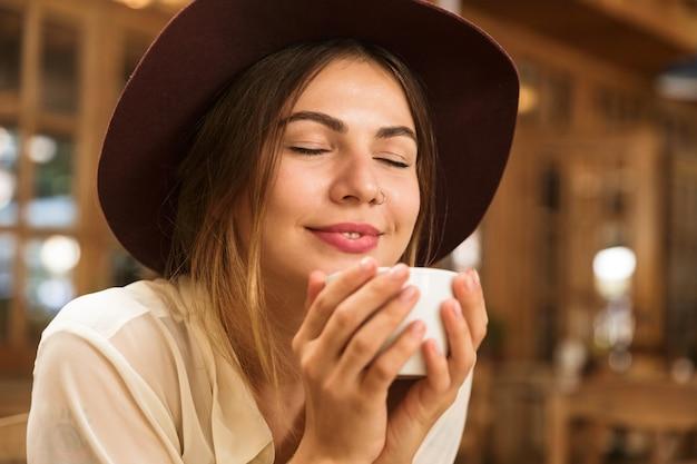 Gros Plan D'une Femme Souriante Au Chapeau Assis à La Table Du Café Photo Premium