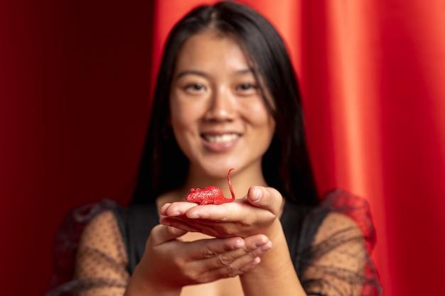 Gros plan d'une femme tenant une figurine de rat pour le nouvel an chinois Photo gratuit
