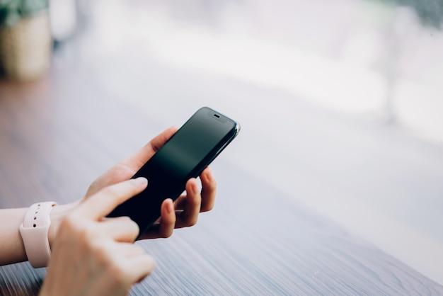 Gros plan d'une femme tenant un smartphone, maquette d'un écran blanc. en utilisant un téléphone portable au café. technologie pour le concept de communication. Photo Premium
