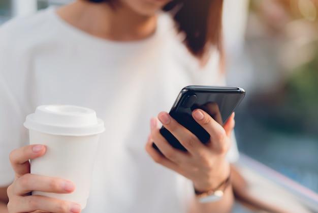 Gros plan d'une femme tenant un smartphone, maquette d'un écran blanc. en utilisant un téléphone portable sur le style de vie. technologie pour le concept de communication. Photo Premium