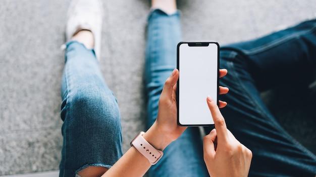 Gros plan d'une femme tenant un smartphone, maquette d'un écran blanc. en utilisant un téléphone portable sur le style de vie. Photo Premium