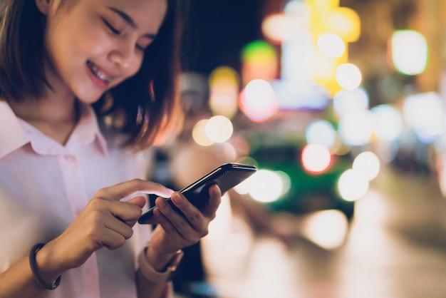 Gros plan d'une femme tenant un smartphone la nuit dans la rue commerçante de la ville et les gens marchent. Photo Premium