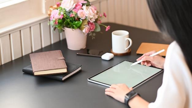 Gros Plan Femme Travaillant Comme Graphiste S'appuyant Sur Une Tablette Informatique à écran Blanc Blanc Tout En étant Assis à La Table De Travail Moderne Avec Salon Confortable Comme Photo Premium