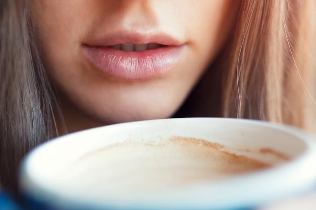 Un gros plan d'une fille boit ses lèvres avec une tasse de café. Photo Premium
