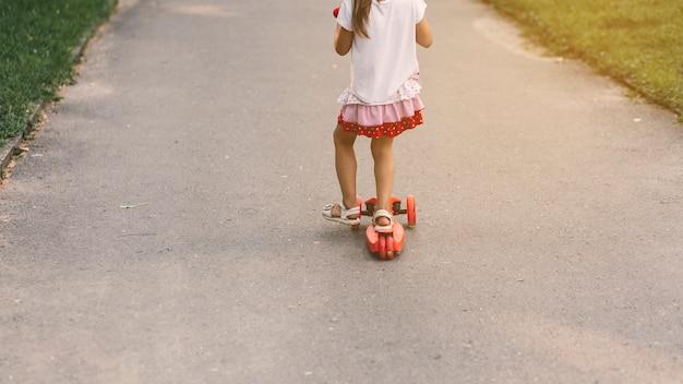Gros plan, fille, équitation, pousser, scooter, rue Photo gratuit