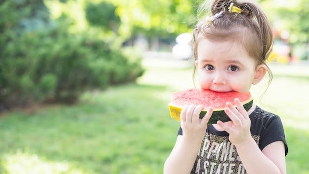 Gros plan, fille, manger, pastèque, parc Photo gratuit