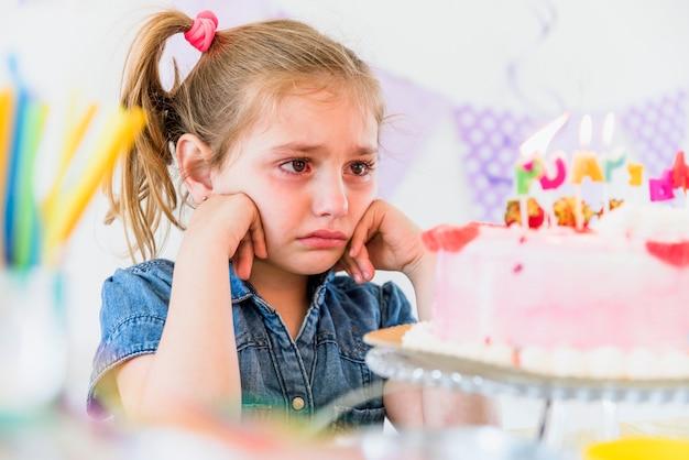 Gros plan d'une fille qui pleure en regardant gâteau d'anniversaire Photo gratuit