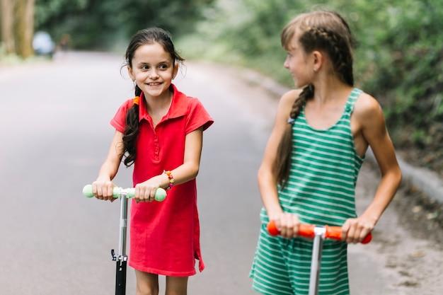 Gros plan, fille, regarder, son, ami, alors, équitation, scooters, sur, route Photo gratuit