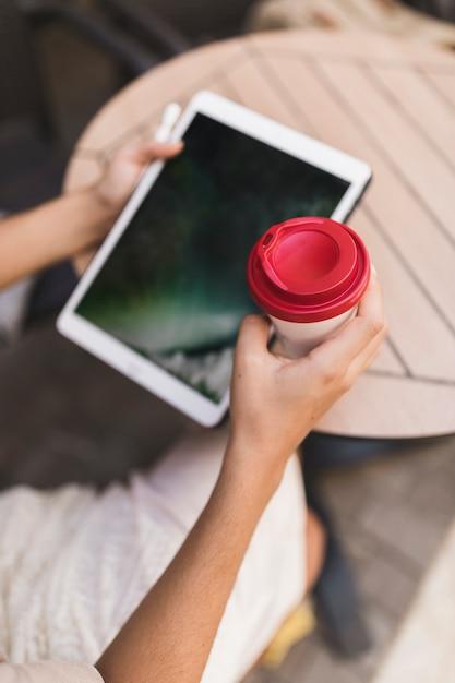 Gros plan d'une fille tenant une tablette numérique et une tasse de café jetable Photo gratuit