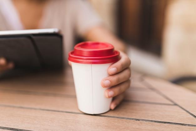 Gros plan d'une fille tenant une tasse de café à emporter sur la table Photo gratuit