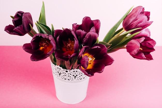 Gros plan, fleurir, tulipes, dans, vase blanc, sur, table rose Photo gratuit