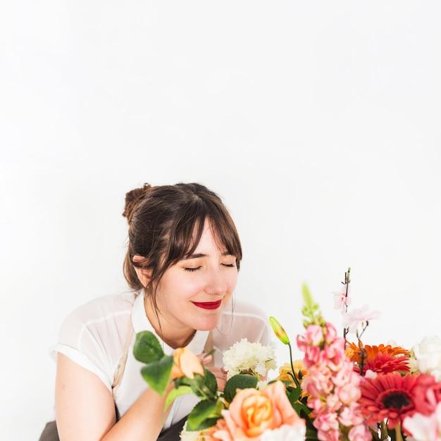 Gros plan, de, a, fleuriste femme, sentir, fleurs, sur, fond blanc Photo gratuit