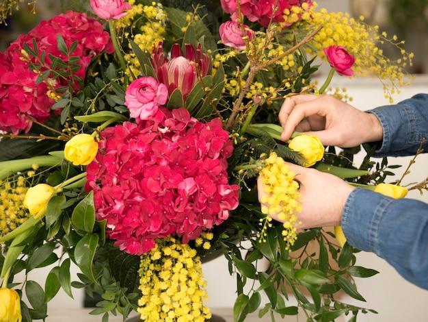 Gros plan, de, fleuriste mâle, main, arrangeant les fleurs dans le vase Photo gratuit