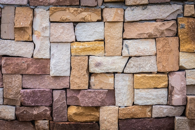 Gros plan de fond de mur de briques anciennes multicolores. Photo Premium