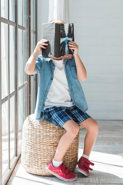 Gros plan d'un garçon assis sur un tabouret en osier près de la fenêtre qui couvre son visage avec un livre Photo gratuit