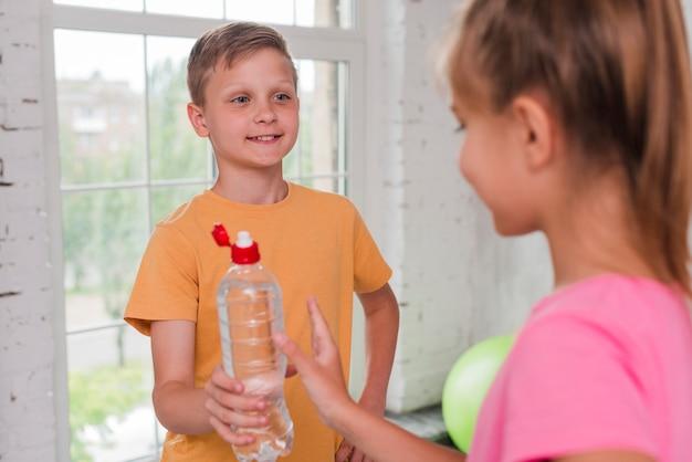 Gros plan d'un garçon donnant une bouteille d'eau à son ami Photo gratuit