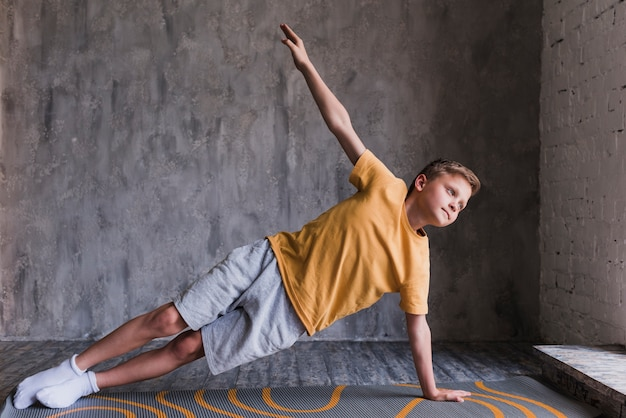 Gros plan, de, a, garçon, faire, stretching, exercer, contre, mur béton Photo gratuit