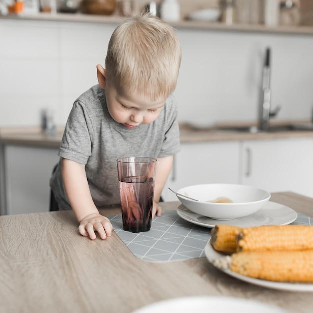 Gros plan d'un garçon mignon blond à la recherche dans le verre de jus Photo gratuit