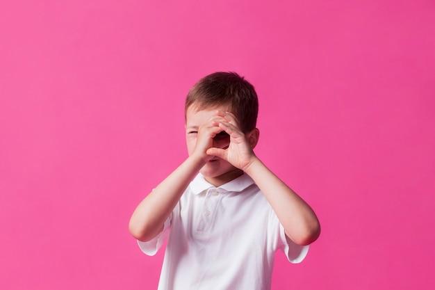 Gros plan, de, garçon, regarder travers, main, jumelles, sur, mur rose, fond Photo gratuit