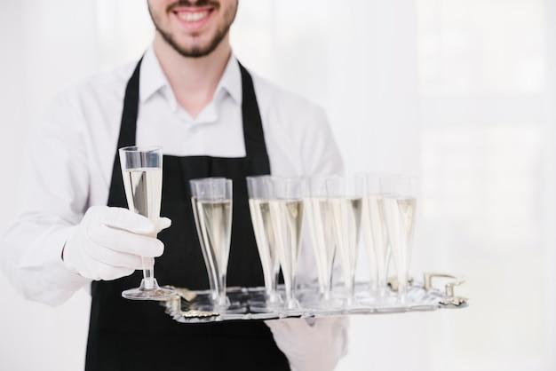 Gros plan garçon tenant des coupes à champagne Photo gratuit