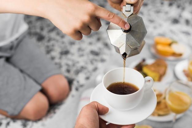 Gros plan d'un garçon versant du café noir dans une tasse Photo gratuit
