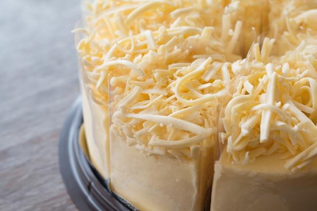 Gros plan de gâteau au fromage sur fond de bureau en bois Photo Premium