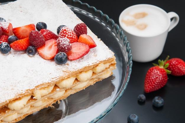 Gros plan d'un gâteau napoléon appétissant avec baies et poudre sucrée Photo gratuit