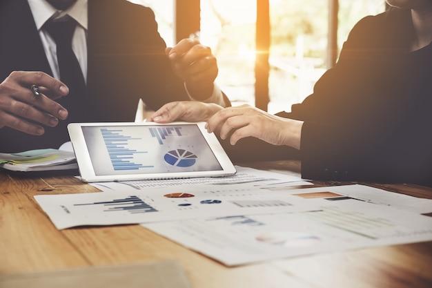 Gros plan de gens d'affaires pointant sur un document d'entreprise sur tablette numérique au cours de la discussion à la réunion. support de groupe et concept de réunion. Photo Premium