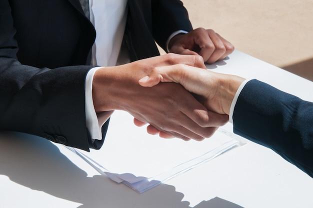 Gros plan de gens d'affaires se serrant la main à l'extérieur Photo gratuit