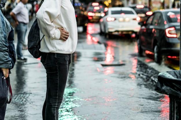 Gros plan des gens qui marchent dans la rue pendant la forte pluie Photo Premium