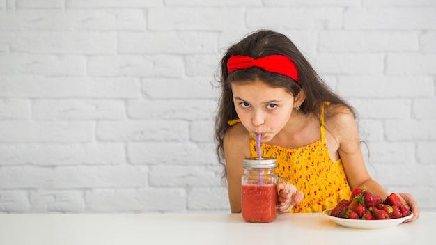 Gros plan, de, a, girl, boire, fraises, smoothies, pot Photo gratuit