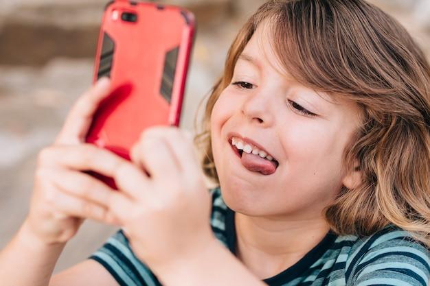 Gros plan, gosse, jouer, téléphone Photo gratuit