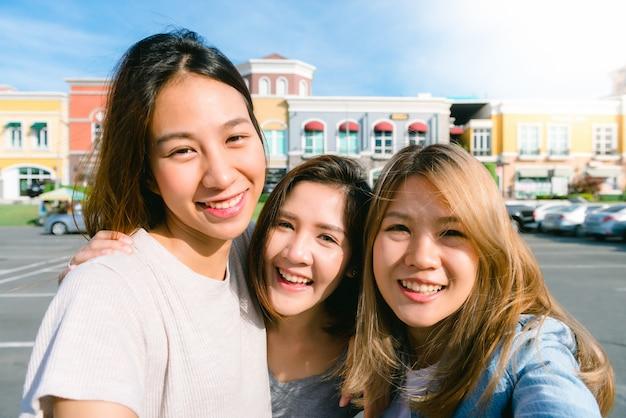Gros plan d'un groupe de jeunes femmes asiatiques se selfie dans la ville des bâtiments en pastel Photo gratuit