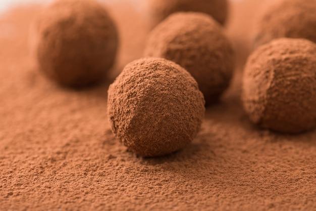 Gros plan d'un groupe de truffes au chocolat noir appétissant recouvertes de poussière de cacao. faible profondeur de champ. Photo Premium