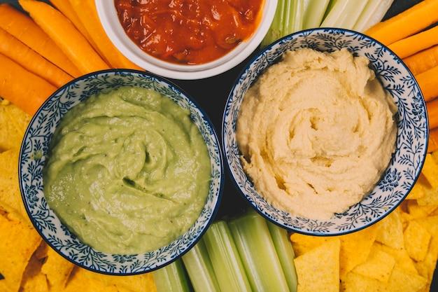 Gros plan de guacamole et de sauce salsa dans un bol sur la carotte; tige de céleri et chips de tortilla Photo gratuit