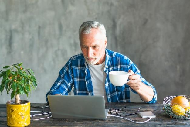 Gros plan, haut, haut, tenue, café, tasse, utilisation, ordinateur portable, chargé, puissance, banque Photo gratuit