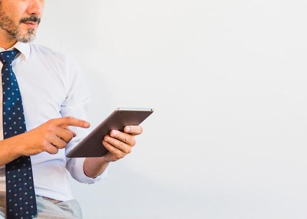 Gros plan d'un homme d'affaires à l'aide d'une tablette numérique sur fond blanc Photo gratuit