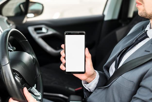 Gros plan d'un homme d'affaires au volant d'une voiture montrant un téléphone portable avec écran blanc Photo gratuit